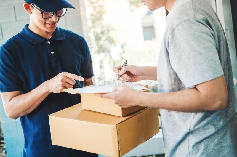 Assinatura do homem do cliente na prancheta para receber em casa o pacote do homem de entrega profissional imagem de stock