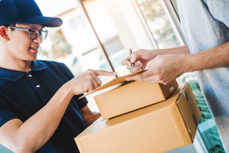Assinatura do homem do cliente na prancheta para receber em casa o pacote do homem de entrega profissional foto de stock royalty free
