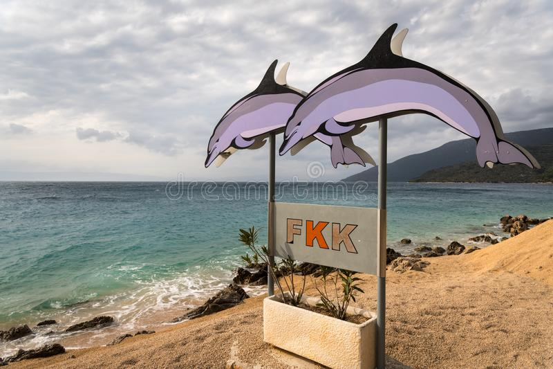 Assine com os dois golfinhos que mostram o começo da praia do nudista foto de stock