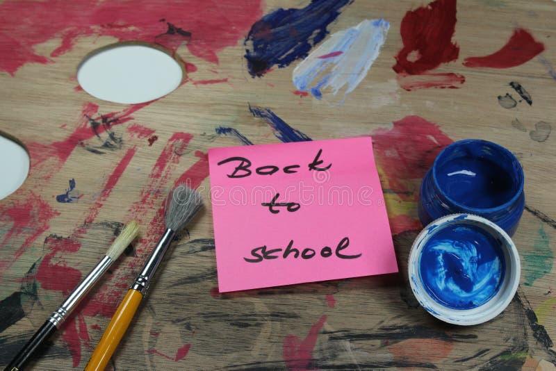 Assine, de volta ao ` da escola na pálete da pintura com ferramentas da pintura fotografia de stock
