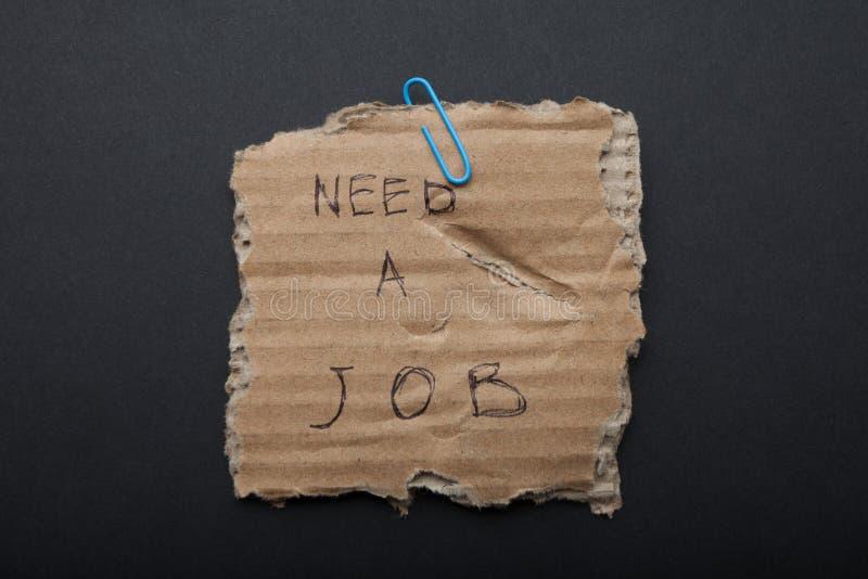 Assine-o 'precisam o trabalho 'no cartão rasgado, fundo preto fotos de stock royalty free