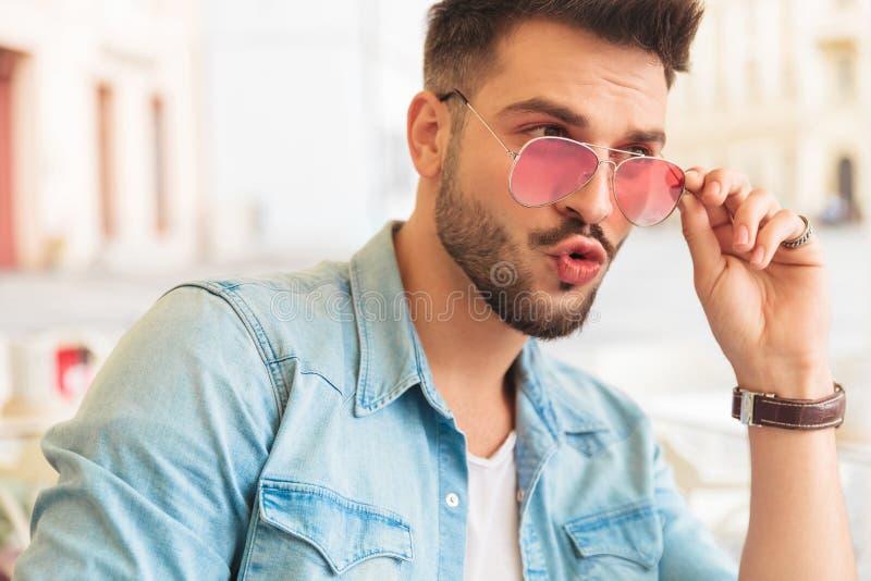 Assis étonnez les lunettes de soleil de fixation d'homme et le regard pour dégrossir photos libres de droits