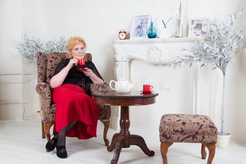 Assis dans un thé potable de femme adulte de chaise images stock