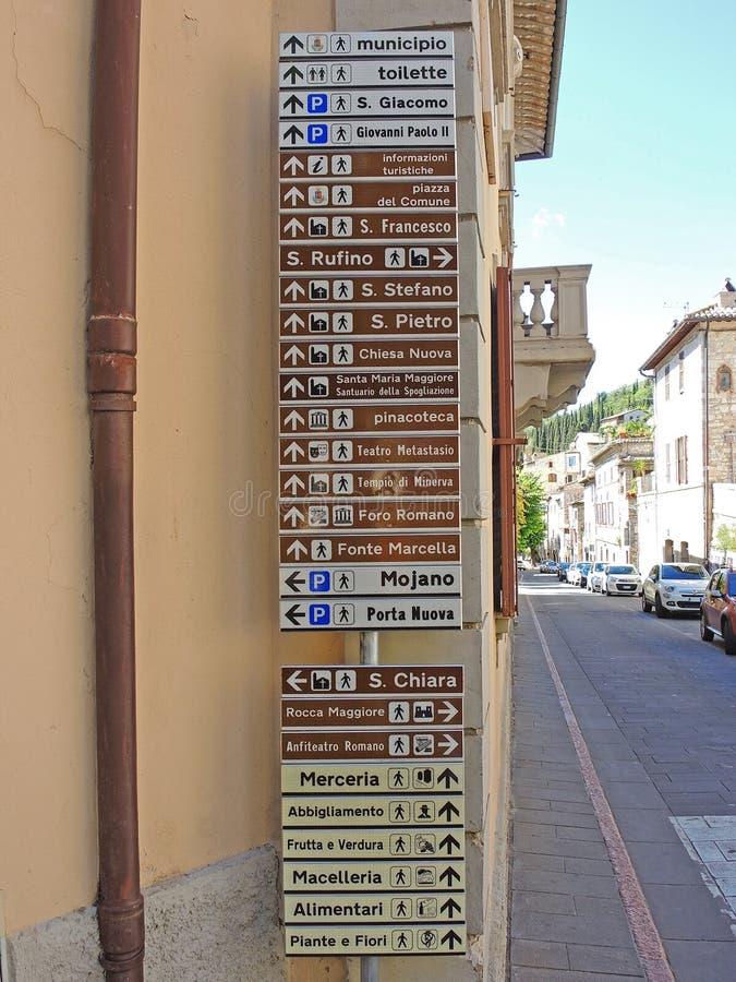 Assisi, Italia Tantissimi segni su scala ridotta che mostrano la direzione di vari monumenti e dei servizi principali immagini stock libere da diritti