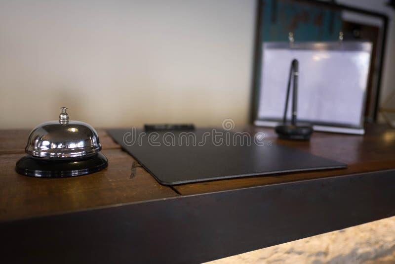 Assista la campana che individua alla ricezione Campana di chiamata d'argento sulla tavola, receptionist su fondo fotografie stock
