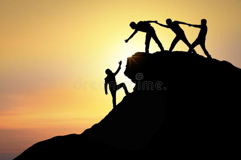 Assistance, teamwork and achievement concept. silhouette of man. Helping friend climbing rock to top and success together stock image