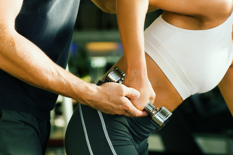 Assistance by the trainer. Young woman lifting a dumbbell in the gym assisted by her personal trainer (Close-up, no faces to be seen