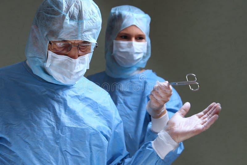 Assistang geeft artsenschaar in op stock afbeeldingen