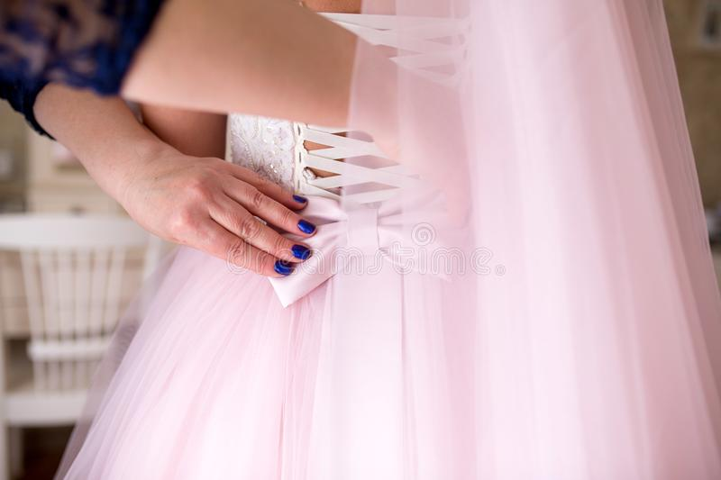 Assistant bow on wedding dress. Assistant straightens bow on wedding dress. Tightly tie ribbons at back waist. Goods for ceremony. This photo is perfect for royalty free stock photo