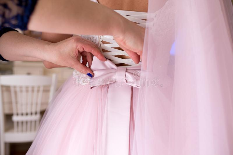 Assistant bow on wedding dress. Assistant straightens bow on wedding dress. Tightly tie ribbons at back waist. Goods for ceremony. This photo is perfect for royalty free stock image