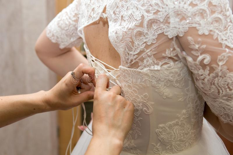 Assistant bow on wedding dress. Assistant straightens bow on wedding dress. Tightly tie ribbons at back waist royalty free stock photo