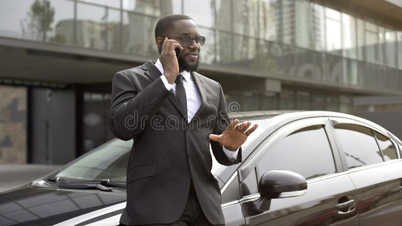 Assistant calming down his boss by phone talking about good outcome of meeting. Stock photo stock photography