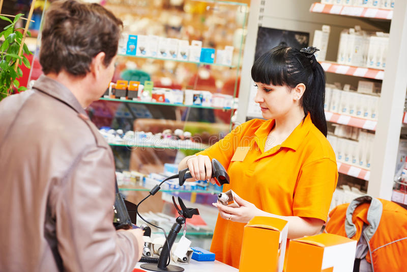 Assistant cashier works with buyer shop. Female seller cashier using barcode scanner during selling lamp to purchaser in hardware shopping mall supermarket royalty free stock image