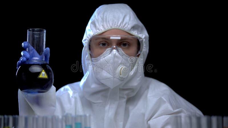 Assistant de laboratoire en costume de protection montrant du liquide toxique, problèmes d'écologie photos libres de droits