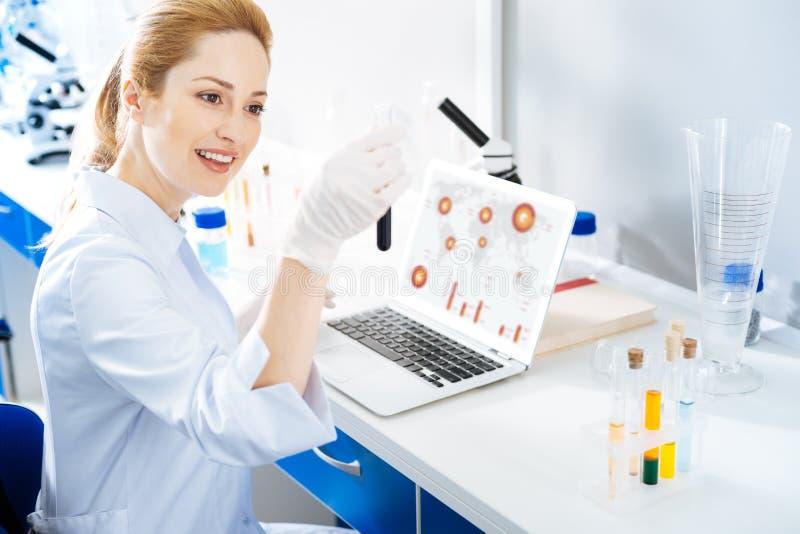 Assistant de laboratoire joyeux vérifiant le tube à essai avec du réactif images libres de droits