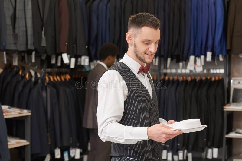 Assistant de magasin choisissant la chemise blanche photo libre de droits