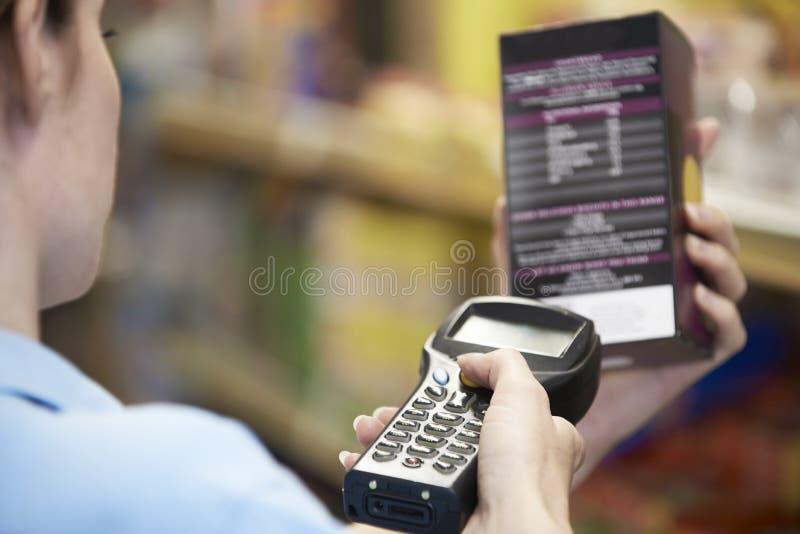 Assistant de ventes vérifiant les niveaux des stocks dans Supmarket utilisant la main il photos stock