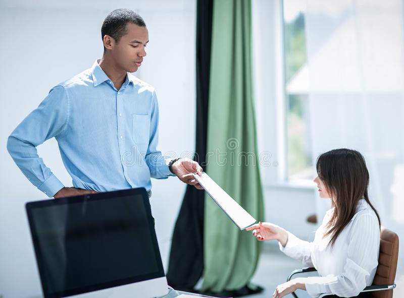 Assistant giving a businessman a working document stock photos