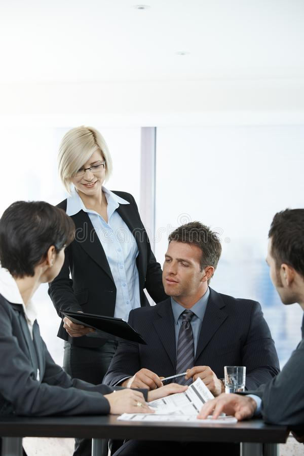 Assistant handing report at meeting. Assistant handing report to executive at meeting in office royalty free stock photos