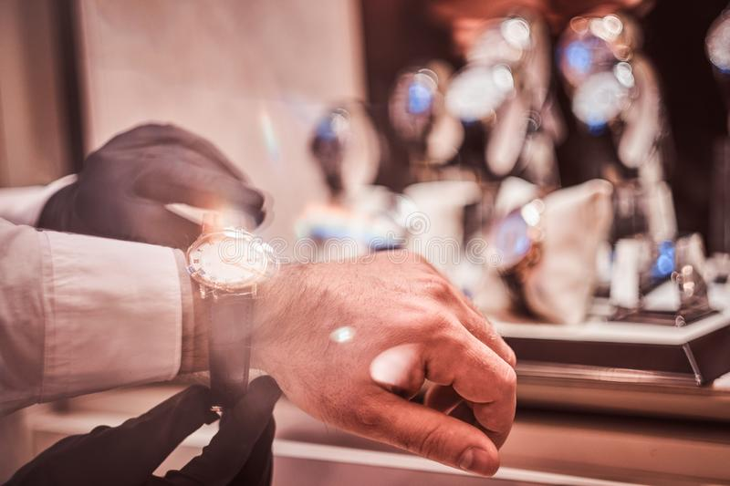 Close-up hands. Assistant helps the client to try on exclusive men`s watches. royalty free stock photography