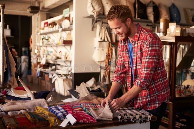 Assistant masculin de ventes arrangeant des textiles dans le magasin de Homeware photographie stock