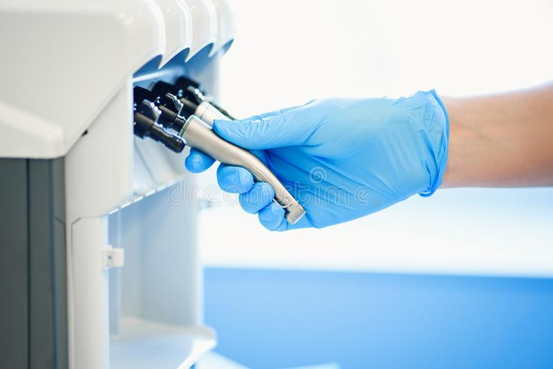 Assistant`s hand in rubber mitt configures dental equipment in dentist`s office. Selective focus. Dentistry and teeth. Close up assistant`s hand in rubber mitt stock photos