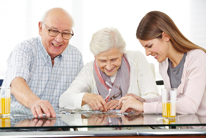 Assistant social résolvant le puzzle denteux images libres de droits