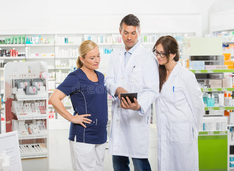 Assistant Using Digital Tablet With Pharmacists stock photos