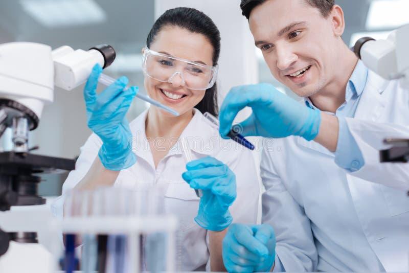 Assistants de laboratoire avec plaisir positifs examinant le nouveau réactif photos libres de droits