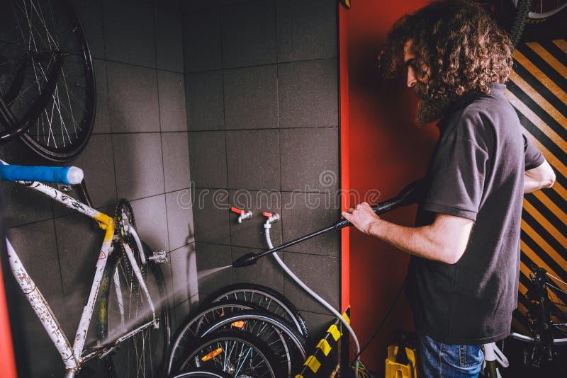 Assiste il lavaggio professionale di una bicicletta nell'officina Un giovane uomo alla moda caucasico con capelli ricci lunghi fa fotografia stock