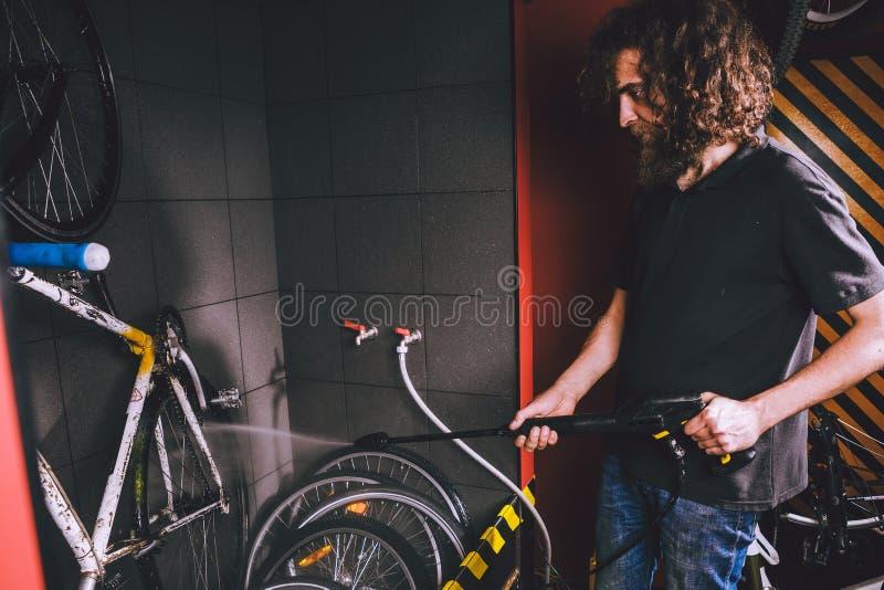 Assiste il lavaggio professionale di una bicicletta nell'officina Un giovane uomo alla moda caucasico con capelli ricci lunghi fa immagini stock libere da diritti