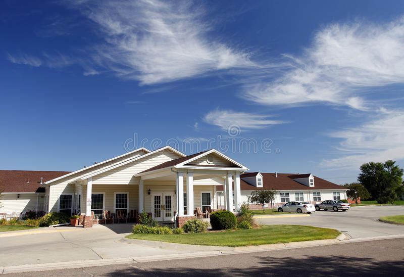 Assisted Living Facility. With red roof, light yellow siding and white trim with green lawn in foreground and blue sky and whispy clouds in background royalty free stock photography