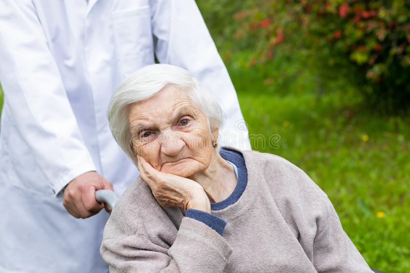 Assisted living. Senior woman with dementia sitting in a wheelchair outdoor, male doctor taking care of her - eldercare stock image