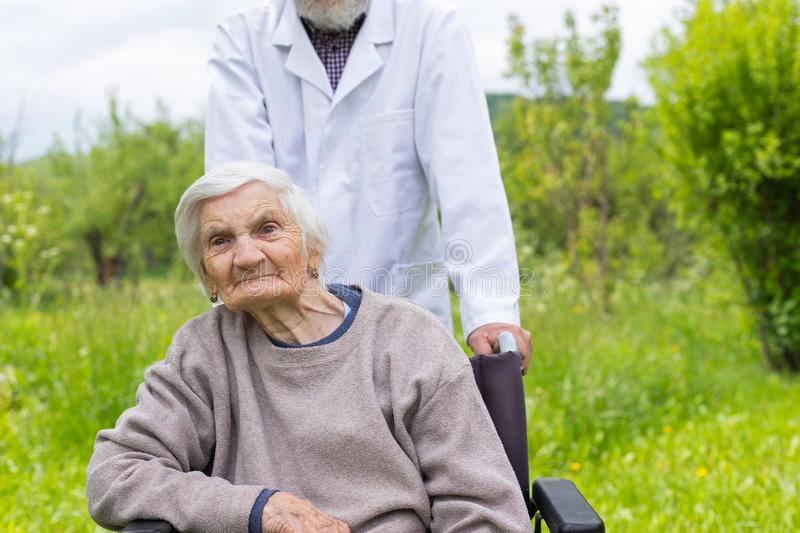 Assisted living. Senior women with dementia sitting in a wheelchair outdoor, male doctor taking care of her - eldercare royalty free stock photography