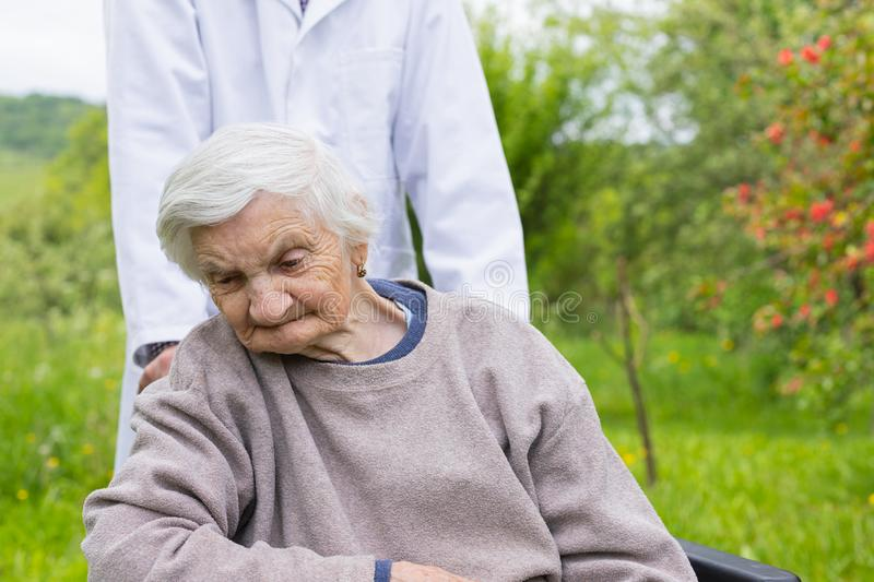 Assisted living. Senior women with dementia sitting in a wheelchair outdoor, male doctor taking care of her - eldercare stock photos