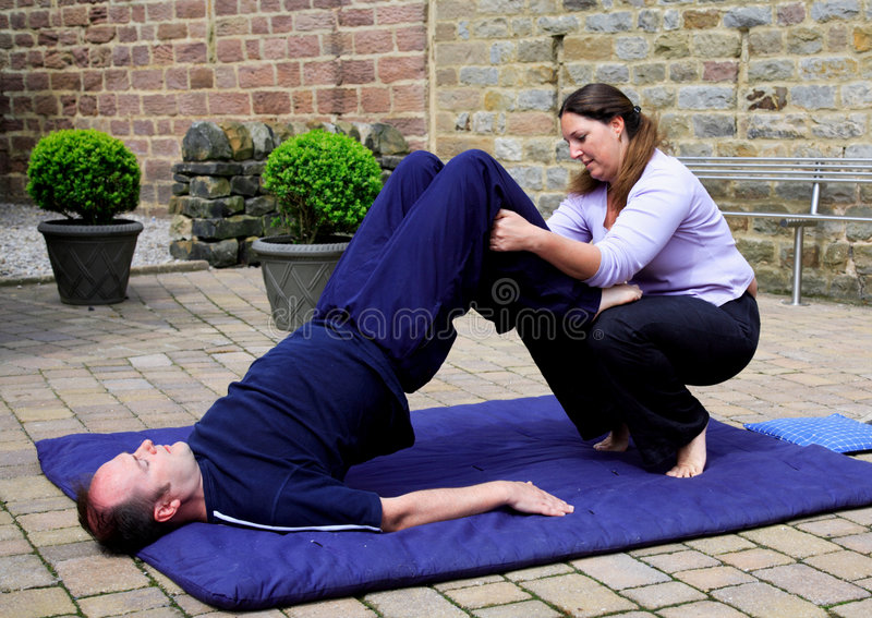 Assisted shoulder stand royalty free stock image