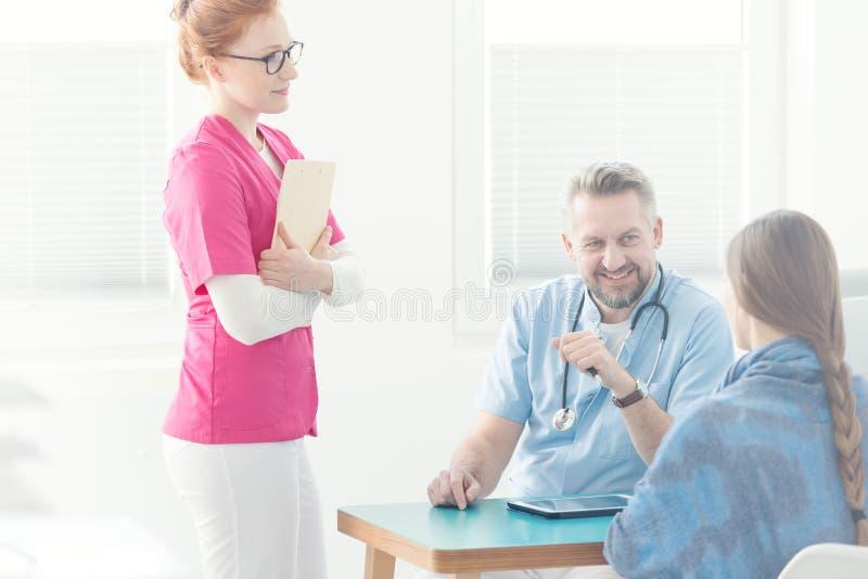 Assistent för doktors` s under medicinsk intervju royaltyfri foto