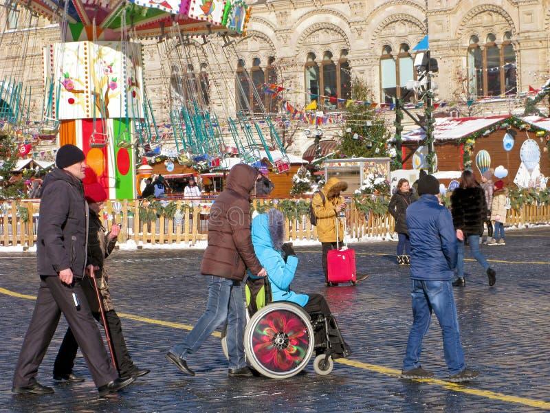 Assistent rörelsehindrad person, rullstol, gata royaltyfri foto