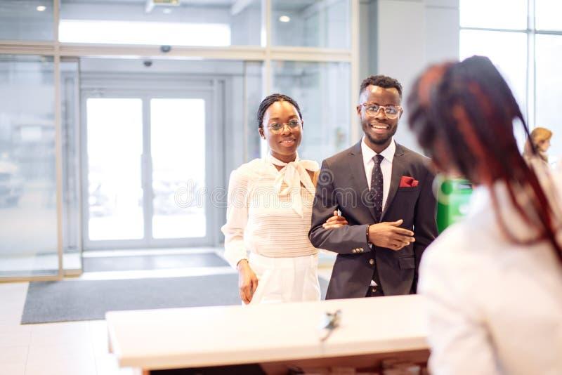 Assistente africano do aluguer de carros que dá a informação a um cliente dos pares imagens de stock royalty free