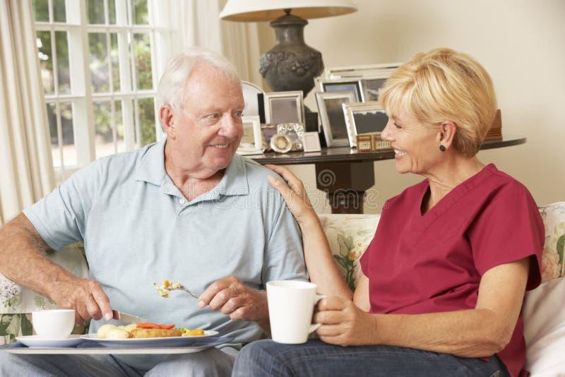 Assistente che serve uomo senior con il pasto nella casa di cura fotografia stock