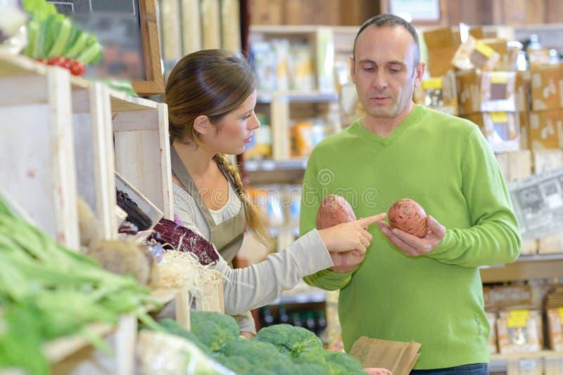 Assistente de compras aconselhando o cliente a segurar batatas fotos de stock