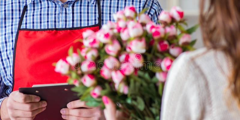 Assistente de florista que vende flores ao cliente f?mea imagens de stock royalty free