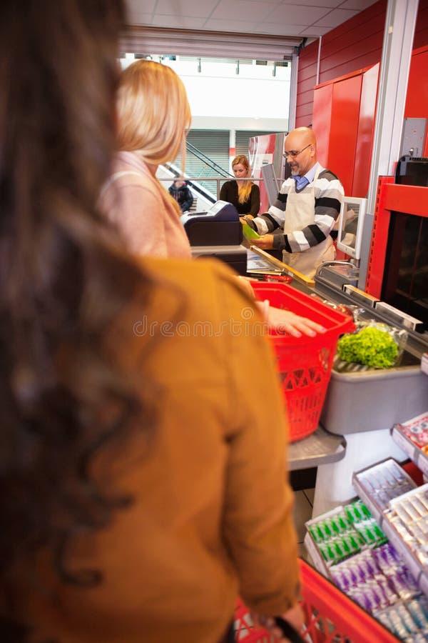 Assistente de loja com clientes imagens de stock royalty free