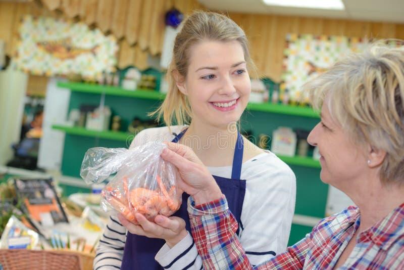 Assistente de loja fêmea que vende peixes frescos no supermercado foto de stock royalty free