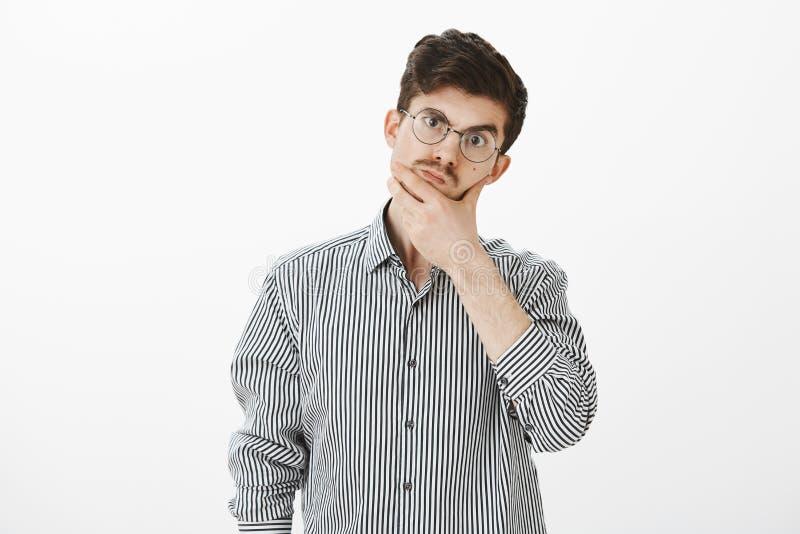 Assistente de loja incomodado para responder na pergunta Indivíduo europeu ordinário inconsciente confuso na camisa e em vidros o fotografia de stock