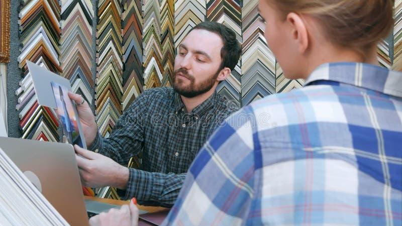 Assistente de loja masculino alegre que conversa com o cliente fêmea, ajudando a escolher o passepartout para o quadro na oficina foto de stock