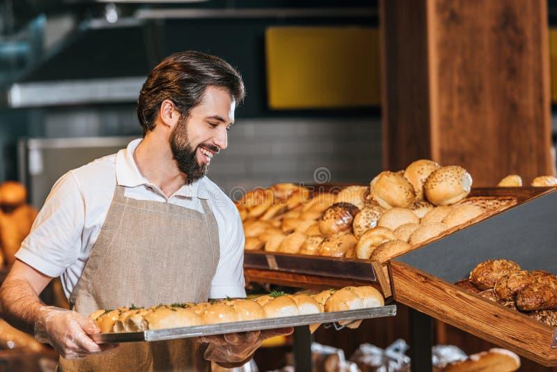 assistente de loja masculino de sorriso que arranja a pastelaria fresca imagens de stock royalty free