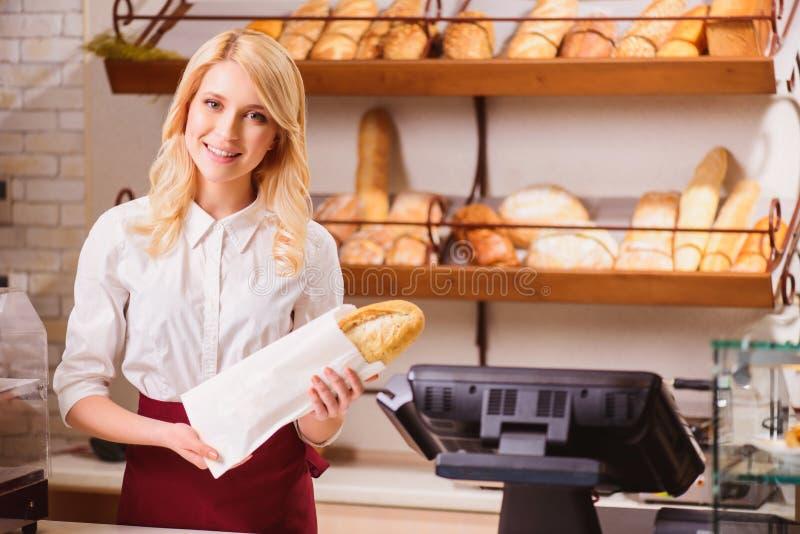 Assistente de loja novo bonito em uma padaria foto de stock royalty free