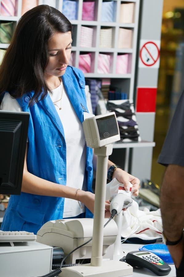Assistente de loja novo que vende a roupa na loja fotografia de stock royalty free