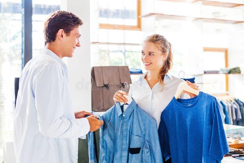 Assistente de loja que ajuda a escolher a roupa foto de stock